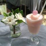 Os batidos da agitação de leite de Rosewater da morango da bebida no café com borrão boken o fundo imagem de stock