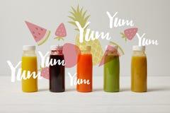 os batidos da desintoxicação em umas garrafas que estão na fileira, refrescam o conceito, yum yum yum inscrição fotos de stock