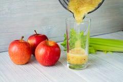 Os batidos feitos das maçãs e do aipo derramaram em um vidro Foto de Stock