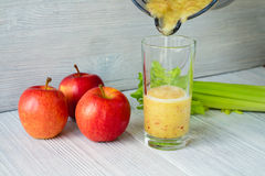 Os batidos feitos das maçãs e do aipo são derramados em um vidro Imagens de Stock