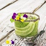 Os batidos frescos do pepino, da hortelã e do mel em um vidro são decorados com flores comestíveis de uma viola do jardim seletiv Fotografia de Stock