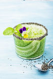 Os batidos frescos do pepino, da hortelã e do mel em um vidro são decorados com flores comestíveis de uma viola do jardim seletiv Imagem de Stock