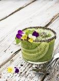 Os batidos frescos do pepino, da hortelã e do mel em um vidro são decorados com flores comestíveis de uma viola do jardim seletiv Imagens de Stock
