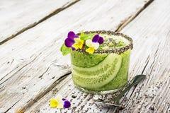 Os batidos frescos do pepino, da hortelã e do mel em um vidro são decorados com flores comestíveis de uma viola do jardim seletiv Imagem de Stock Royalty Free