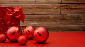 Os baubels de brilho vermelhos e um vermelho envolveram o presente que encontra-se em uma tabela vermelha imagens de stock royalty free