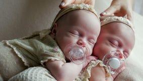 Os bebês gêmeos dormem na ucha nos vestidos video estoque