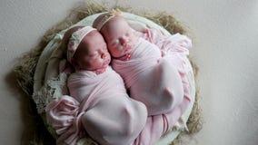 Os bebês gêmeos dormem na ucha nos vestidos filme