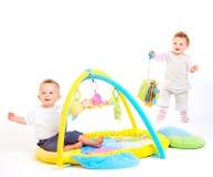 Os bebês jogam com brinquedos Fotos de Stock