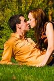 Os beijos novos felizes dos pares em uma grama Fotografia de Stock