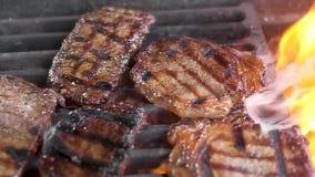 Os bifes suculentos da carne estão na grade A carne ? fritada no inc?ndio H? um fumo A c?mera move-se da esquerda para a direita  vídeos de arquivo