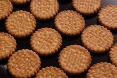 Os biscoitos que encontram-se nas fileiras em um preto envernizaram a superfície Fotografia de Stock Royalty Free