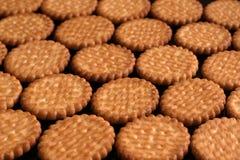 Os biscoitos que encontram-se nas fileiras em um preto envernizaram a superfície Fotos de Stock Royalty Free