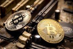 Os bitcoins do ouro e da prata no fundo de um computador eletrônico queimado embarcam imagem de stock royalty free