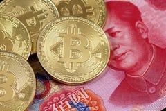 Os bitcoins dourados fecham-se acima com uma nota de 100 yuan Fotografia de Stock Royalty Free