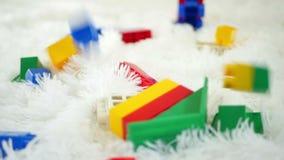 Os blocos coloridos do brinquedo caem de cima em um fundo branco, close-up filme