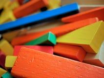 Os blocos de apartamentos de madeira das crianças coloridos brilhantemente em Toy Box Imagem de Stock Royalty Free