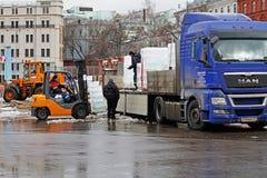 Os blocos de gelo da carga dos trabalhadores na auto plataforma dos caminhões no quadrado da revolução após o ` nacional do festi Fotografia de Stock