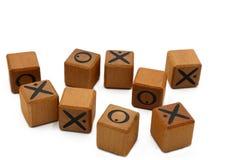 Os blocos de madeira com x e O nele isolaram-se no fundo branco imagem de stock