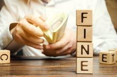 Os blocos de madeira com a multa da palavra e o homem calculam o tamanho da multa O conceito da puni??o financeira Pena como a imagens de stock