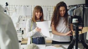 Os bloggers bonitos novos dos desenhadores de moda das mulheres estão gravando o vídeo com a câmera sobre costurar o vestuário no video estoque