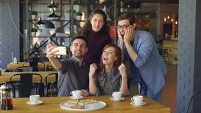 Os bloggers populares alegres dos jovens estão tomando o selfie que levanta o riso e ter do divertimento no café Tecnologia moder vídeos de arquivo