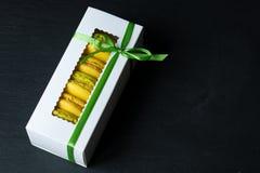 Os bolinhos de amêndoa amarelam em um fundo preto em uma caixa branca Imagem de Stock