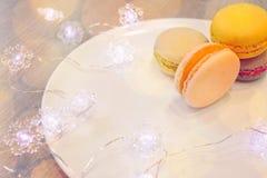 Os bolinhos de amêndoa brilhantes encontram-se em uma placa e em uma festão com luzes imagens de stock royalty free
