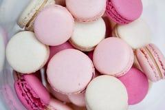 Os bolinhos de amêndoa carmesins brancos cor-de-rosa encontram-se em um vaso transparente Fotos de Stock