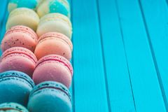 Os bolinhos de amêndoa coloridos encontram-se em seguido em um fundo de madeira de turquesa, cookies de amêndoa em tons pasteis,  Fotos de Stock