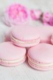 Os bolinhos de amêndoa cor-de-rosa delicados com aumentaram na madeira Imagem de Stock Royalty Free