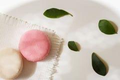 Os bolinhos de amêndoa cor-de-rosa, brancos no fundo claro, saltam as pétalas verdes, guardanapo branco Vista superior Manhã româ Foto de Stock