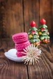 Os bolinhos de amêndoa cor-de-rosa com decorações do Natal woooden sobre o fundo Fotografia de Stock