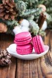 Os bolinhos de amêndoa cor-de-rosa com decorações do Natal woooden sobre o fundo Fotos de Stock Royalty Free