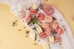 Os bolinhos de amêndoa cor-de-rosa e brancos endurecem com as flores em botão grandes e pequenas AR Fotografia de Stock Royalty Free
