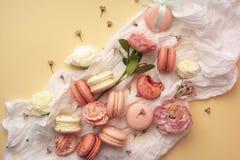 Os bolinhos de amêndoa cor-de-rosa e brancos endurecem com as flores em botão grandes e pequenas AR Imagem de Stock