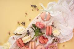 Os bolinhos de amêndoa cor-de-rosa e brancos endurecem com as flores em botão grandes e pequenas AR Fotos de Stock Royalty Free