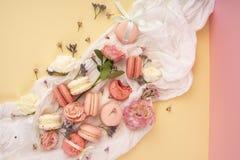 Os bolinhos de amêndoa cor-de-rosa e brancos endurecem com as flores em botão grandes e pequenas AR Imagem de Stock Royalty Free