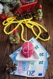Os bolinhos de amêndoa cor-de-rosa e vinte euro com decorações do Natal woooden sobre o fundo Imagens de Stock Royalty Free