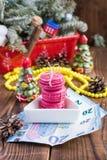 Os bolinhos de amêndoa cor-de-rosa e vinte euro com decorações do Natal woooden sobre o fundo Imagem de Stock
