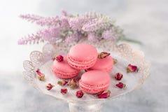 Os bolinhos de amêndoa cor-de-rosa em um vintage chapeiam e secaram flores em botão pastel Fotos de Stock Royalty Free