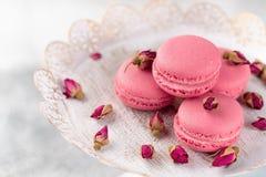 Os bolinhos de amêndoa cor-de-rosa em um vintage chapeiam e secaram flores em botão pastel Fotografia de Stock Royalty Free