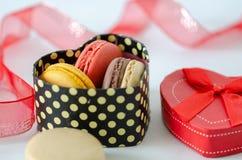 Os bolinhos de amêndoa franceses estão em uma caixa de presente, o dia de Valentim, foto de stock