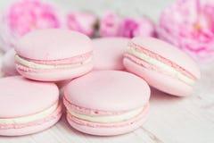 Os bolinhos de amêndoa cor-de-rosa delicados com aumentaram na madeira Foto de Stock Royalty Free