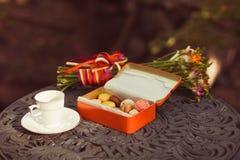 Os bolinhos e o copo de chá seriram na tabela Imagens de Stock
