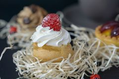 Os bolos divinos com framboesas e creme, o fundo são borrados com o outro cak fotografia de stock royalty free