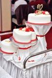 Os bolos doces sob a forma das rosas vermelhas decoram o bolo de casamento com os galhos mais decorativos do creme branco Foto de Stock Royalty Free