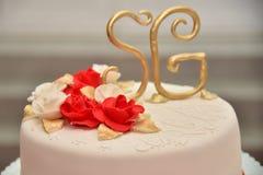 Os bolos doces sob a forma das rosas vermelhas decoram o bolo de casamento com os galhos mais decorativos do creme branco Imagens de Stock Royalty Free