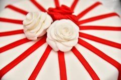 Os bolos doces sob a forma das rosas vermelhas decoram o bolo de casamento com os galhos mais decorativos do creme branco Foto de Stock