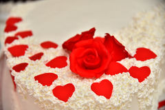 Os bolos doces sob a forma das rosas vermelhas decoram o bolo de casamento com os galhos mais decorativos do creme branco Fotografia de Stock Royalty Free