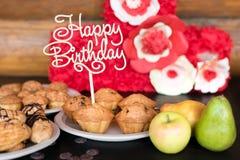 Os bolos e os queques de aniversário com cumprimento de madeira assinam no fundo rústico De madeira cante com feliz aniversario d Imagem de Stock